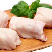 Fresh chicken thighs on a wooden chopping board - shallow depth of field - white background